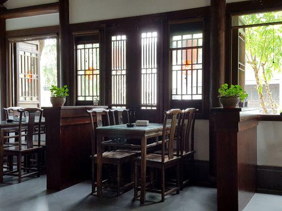 旅店在仓河北街的东头,仿古民居风格。门面不大,但进去后,大堂兼茶室,估计有七八十平米,临河而建,木质桌椅,装饰上透露着古风之意。想来在此喝喝茶、看看河、发发呆,一定很惬意的。进小镇后,可着沿河边,走仓河北街或仓河南街,一路往东,即可达客栈。客栈边上就是饭店,对面是土菜馆,东面边上是一家很不错的饭店。原订的是临河的观景标房,店家客气,免费升为临河观景套房,在二楼。房间很大,床边还有一沙发,可睡人,推窗见河,一株柳树,绿叶映窗,美且有意境。客栈的建筑是砖木结构,原木栋梁,有个漂亮的天井庭院,一汪池水,花盆盆景